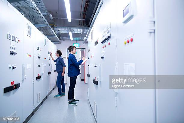 full length side view of colleges in control room back to back looking at switchgear - sigrid gombert fotografías e imágenes de stock