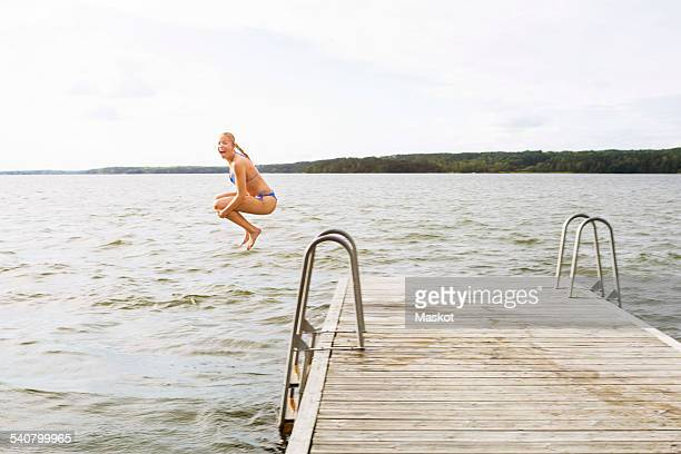 Full length side view of excited woman jumping into lake