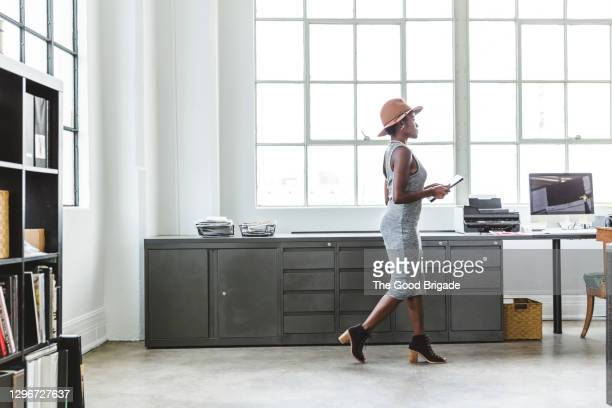 full length side view of fashionable businesswoman holding digital tablet while walking at creative workplace - side view stock pictures, royalty-free photos & images