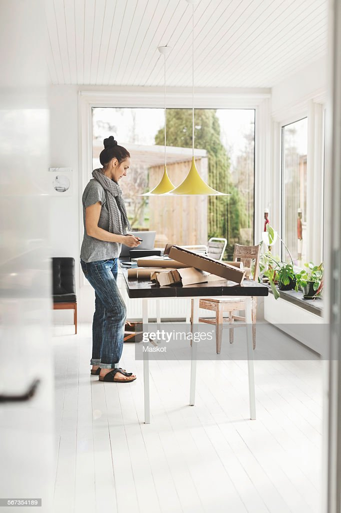 Full Length Side View Of Female Architect Working At Table In Home ...