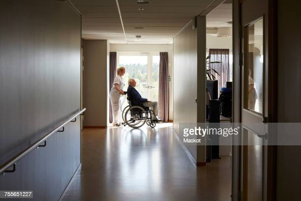 Full length side view of female nurse pushing senior man on wheelchair at hospital corridor