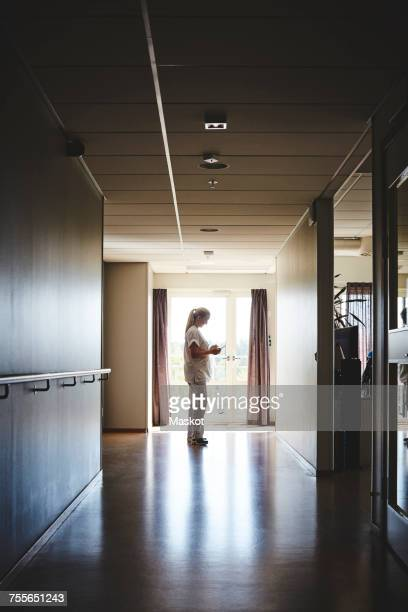 Full length side view of female nurse using digital tablet in hospital corridor