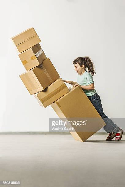 Full length side view of girl dropping boxes in house