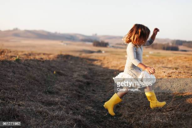 full length side view of girl running on field - rubber boot stock pictures, royalty-free photos & images