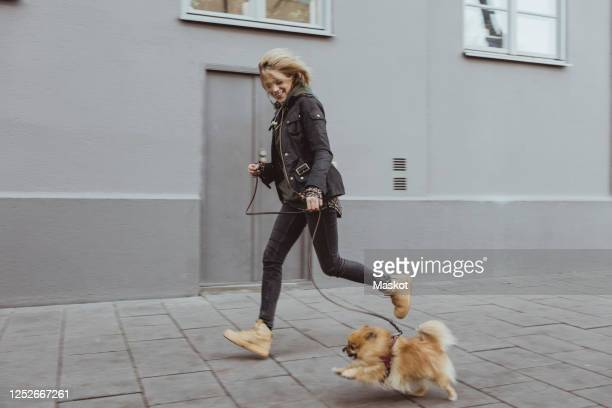 full length side view of happy woman running with her pomeranian dog on footpath by building in city - pet lead stock pictures, royalty-free photos & images