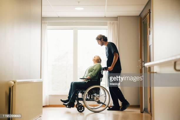 full length side view of male nurse pushing disabled senior woman on wheelchair in alley at retirement home - community care stock pictures, royalty-free photos & images