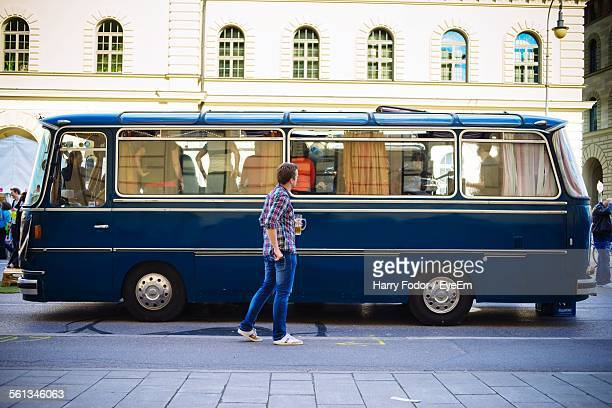 Full Length Side View Of Man Standing By Bus On Street