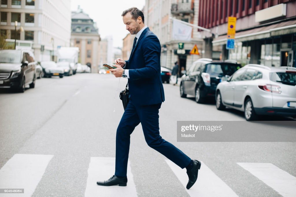Full length side view of mature businessman crossing street while using smart phone in city : Stockfoto
