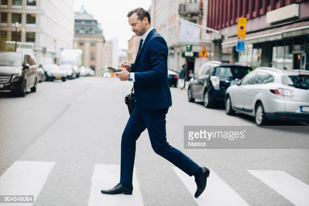 full length side view of mature businessman crossing street while using smart phone in city - passageiro diário - fotografias e filmes do acervo
