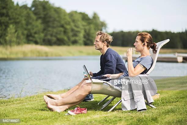 Full length side view of mature couple relaxing on desk chairs at lakeshore