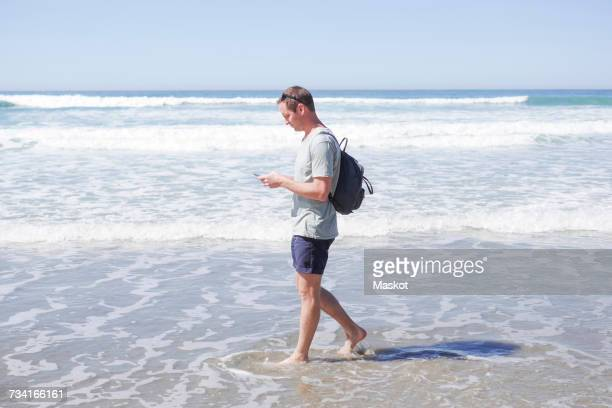Full length side view of mature man using mobile phone while walking in sea at beach