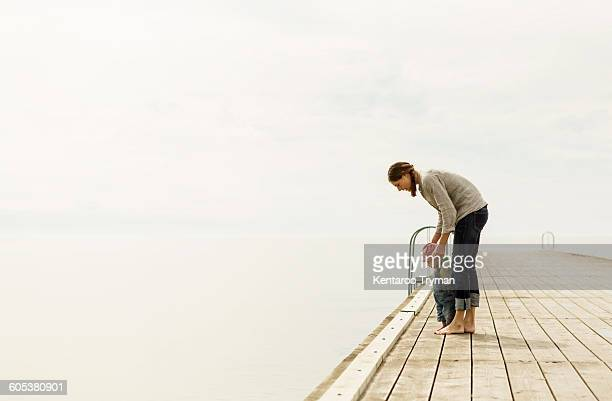 Full length side view of mother and baby girl standing on pier at sea against sky