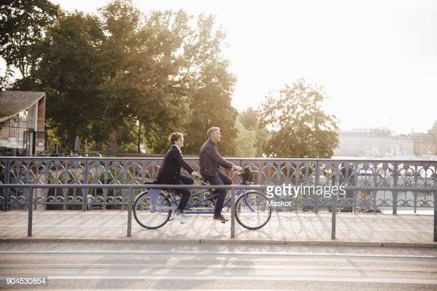 full length side view of senior couple enjoying tandem bike ride on bridge - tandem bicycle stock pictures, royalty-free photos & images