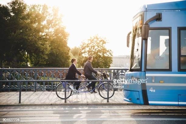 full length side view of senior couple riding tandem bike on bridge - stockholm fotografías e imágenes de stock