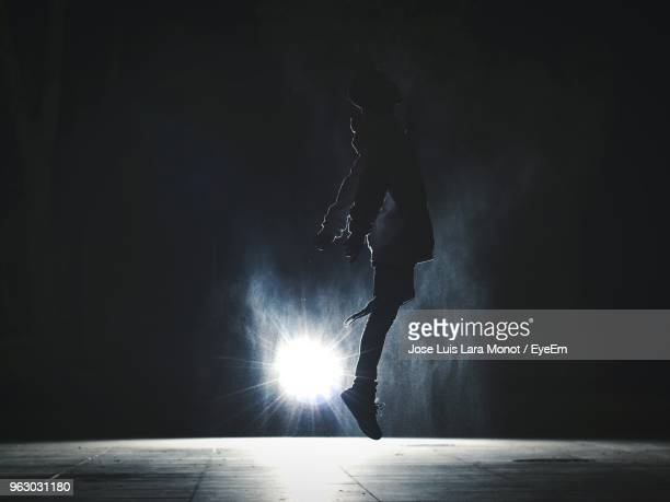 full length side view of silhouette man jumping against illuminated spot light at night - back lit stock pictures, royalty-free photos & images