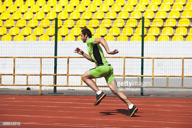 Full length side view of sporty young man running on race track in stadium