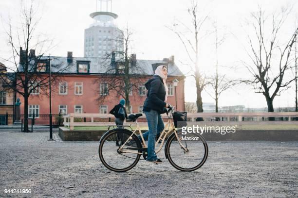 Full length side view of teenage girl wearing hijab cycling in city