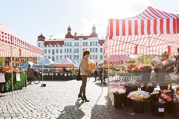 full length side view of woman buying flowers at market stall - markt stockfoto's en -beelden