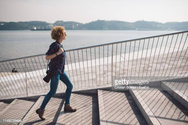 full length side view of woman climbing steps with sea in background - bortes stockfoto's en -beelden