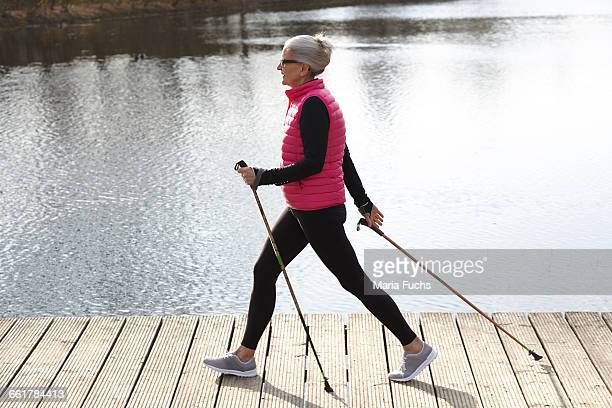 Full length side view of woman nordic walking by pond