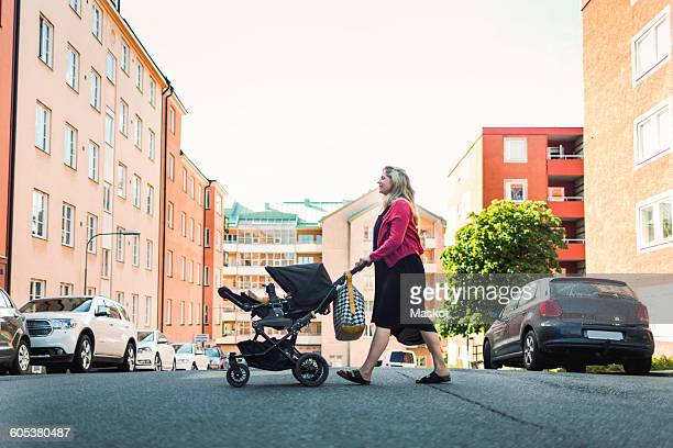 Full length side view of woman pushing baby in carriage crossing city street