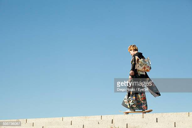 full length side view of woman skateboarding against clear blue sky - tradition stock pictures, royalty-free photos & images