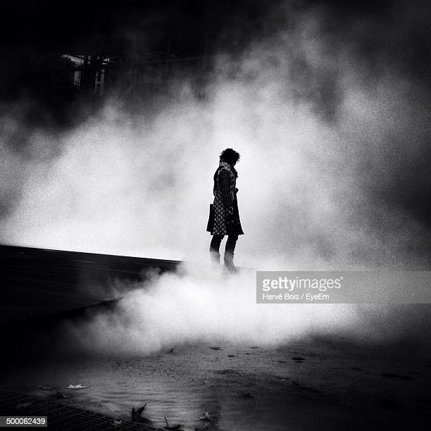 Full length side view of woman surrounded by smoke at night