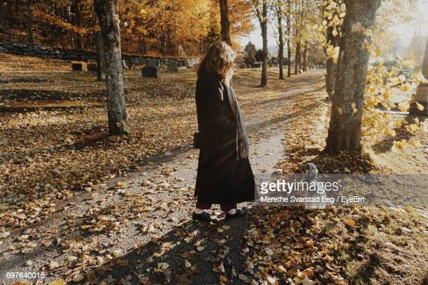 Full Length Side View Of Woman Walking By Dog At Park During Autumn