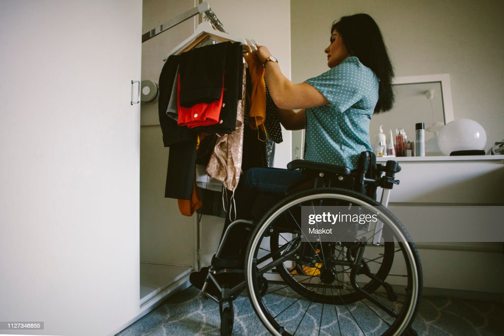 Full length side view of young disabled woman looking at clothes hanging in wardrobe : Stock Photo