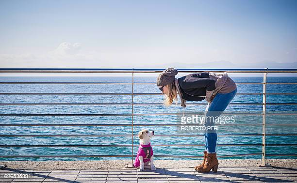 Full length side view of young woman by railings in front of ocean bending over looking at dog