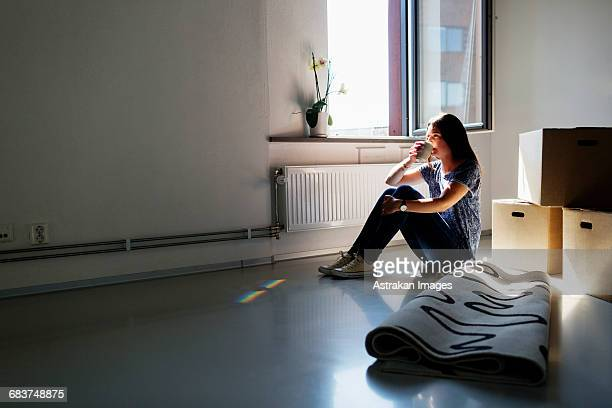 Full length side view of young woman having coffee in new house