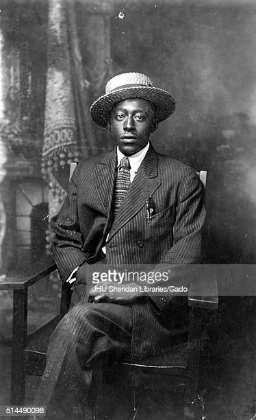 Full length sitting portrait of mature African American man wearing dark  striped suit tie with design 149a47b589c3