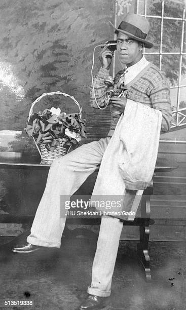 Full length sitting portrait of young African American man wearing light pants light shirt striped tie and patterned sweater holding telephone and...