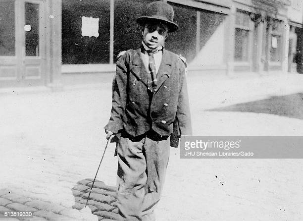 Full length standing portrait of African American child, dressed up as Charlie Chaplin wearing over-sized coat and pants, tie and bowler hat,...