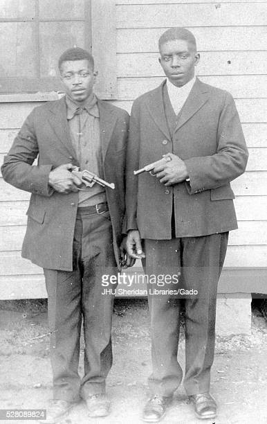 Full length standing portrait of two African American men with neutral expressions standing outside of a building and pointing handguns at one...