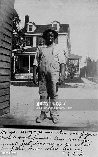 Full length standing portrait of young African American man with a neutral expression in front of a house wearing a hat and overalls 1906