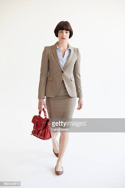 full length studio shot of businesswoman with red handbag - beige stock pictures, royalty-free photos & images