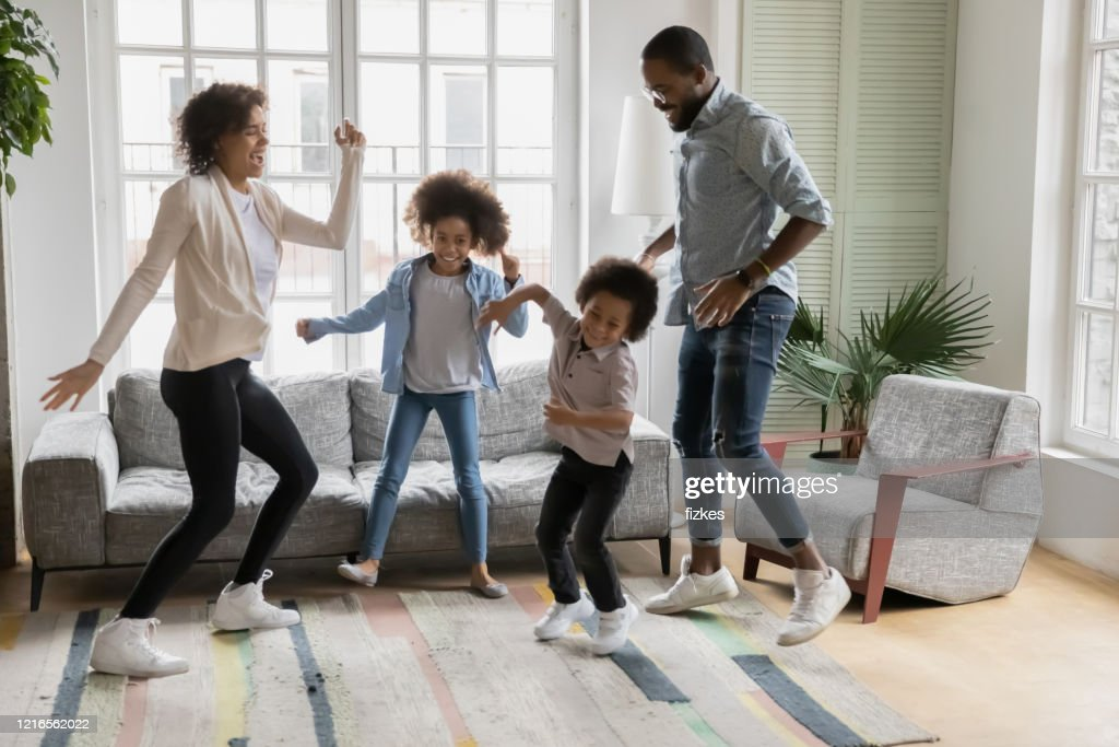 Full length view African ethnicity family dancing in living room : Stock Photo