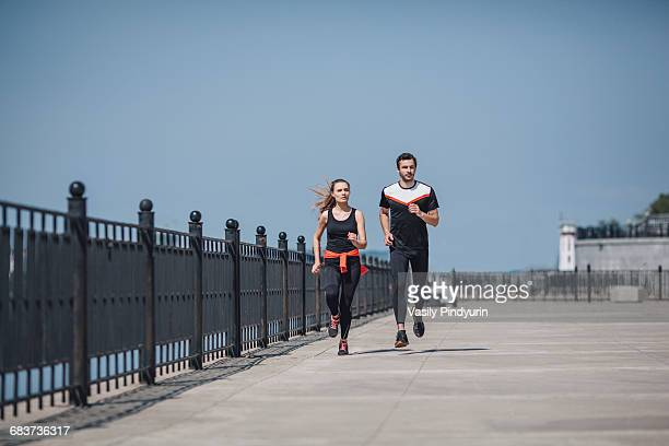 Full length view of friends running on promenade against clear sky