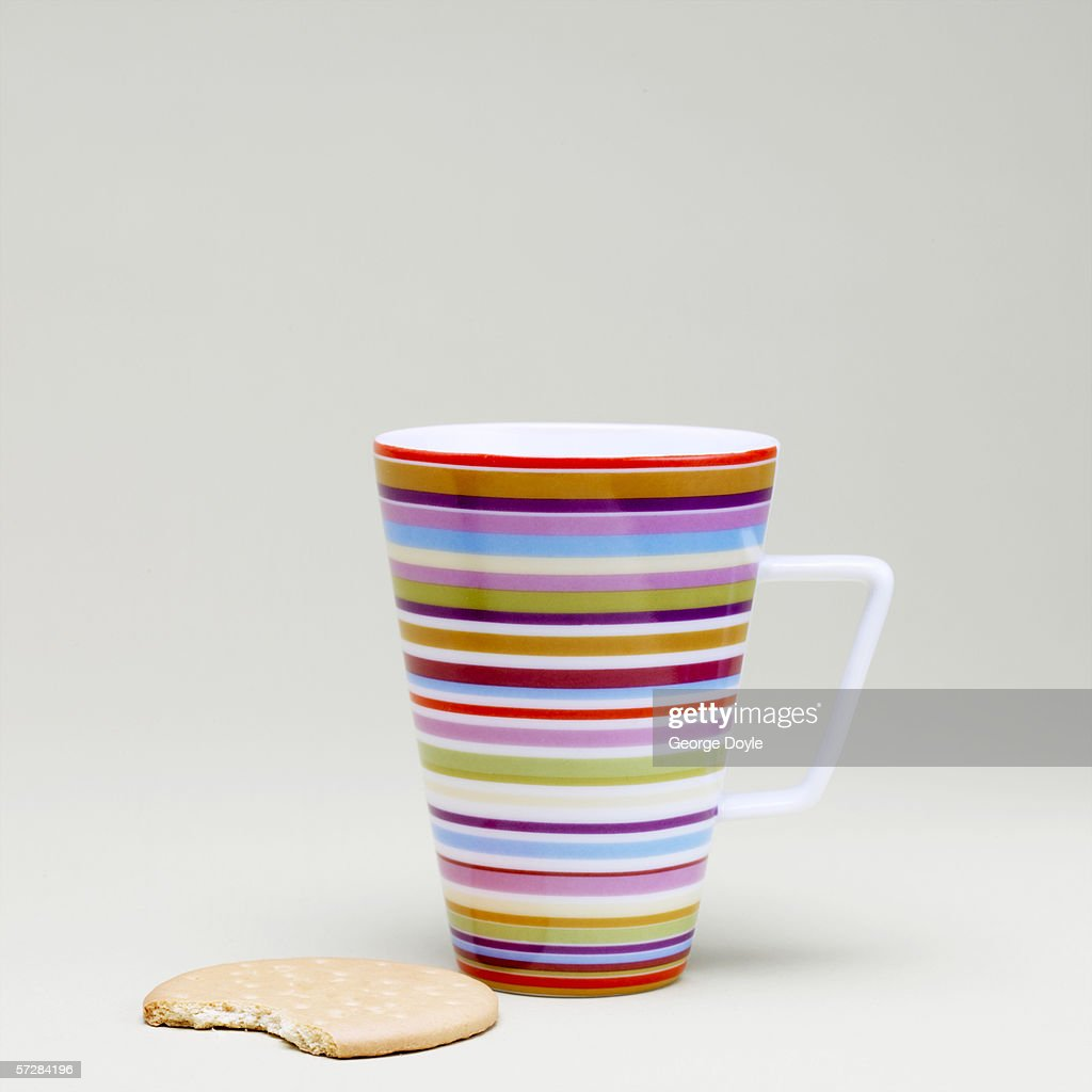 Full length view of mug and biscuit : Stock Photo
