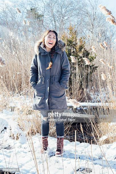 full length view of woman wearing winter coat on snowy landscape looking at camera smiling - 毛皮の飾り ストックフォトと画像