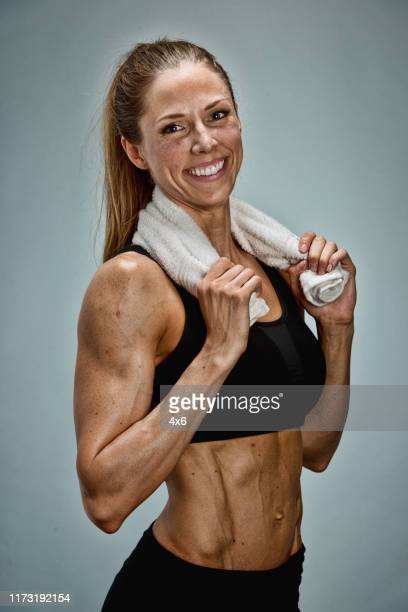 full length / waist up / front view / looking at camera of 20-29 years old adult beautiful / ponytail caucasian female / young women fitness instructor / customer / instructor standing in front of gray background wearing sports bra / bra / shorts - 25 29 years stock pictures, royalty-free photos & images
