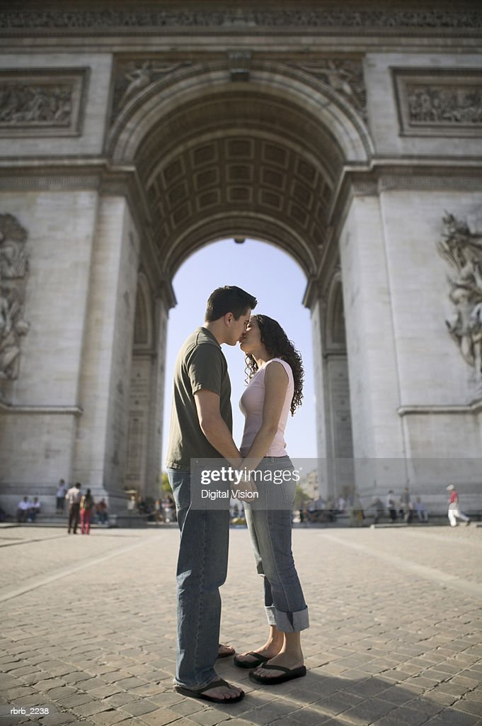 full length wide shot of a young adult couple as they kiss at the arc of triumph in paris : Foto de stock