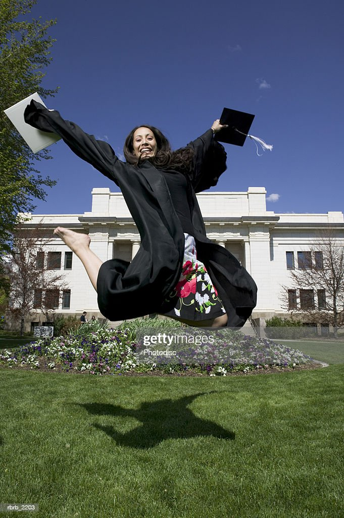 full length wide shot of a young adult female college graduate as she jumps through the air : Foto de stock