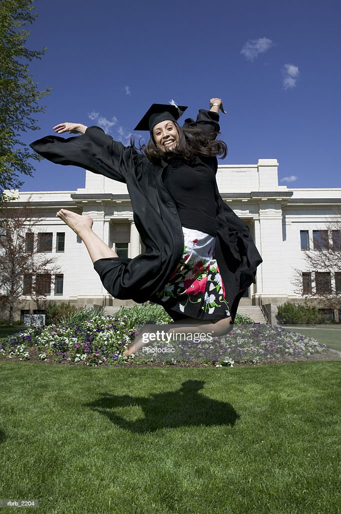full length wide shot of a young adult female college graduate as she excitedly jumps through the air : Foto de stock