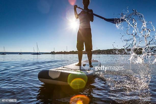 Full Length Woman Paddleboarding In Lake