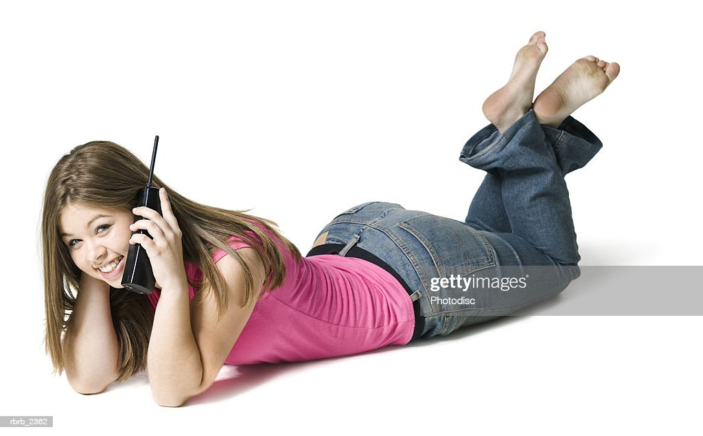 full length youth portrait of a teenage female as she lays down and chats on the phone : Foto de stock