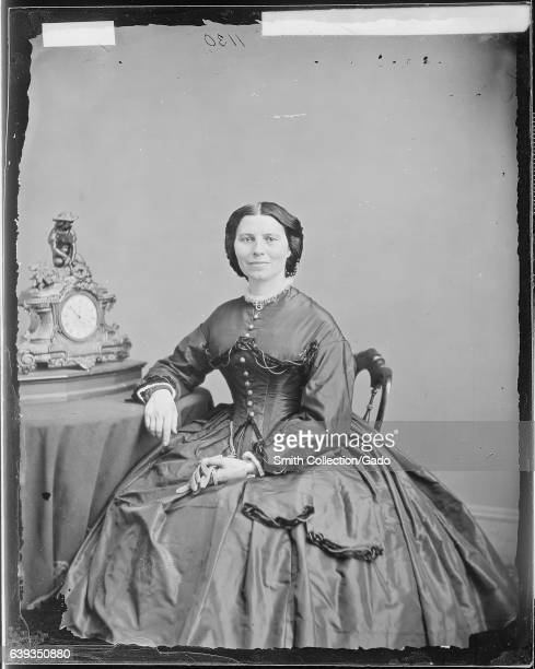FUll lentgh portriat of nurse and founder of the American Red Cross Clara Barton seated at a table on which rests a clock 1863 Image courtesy...