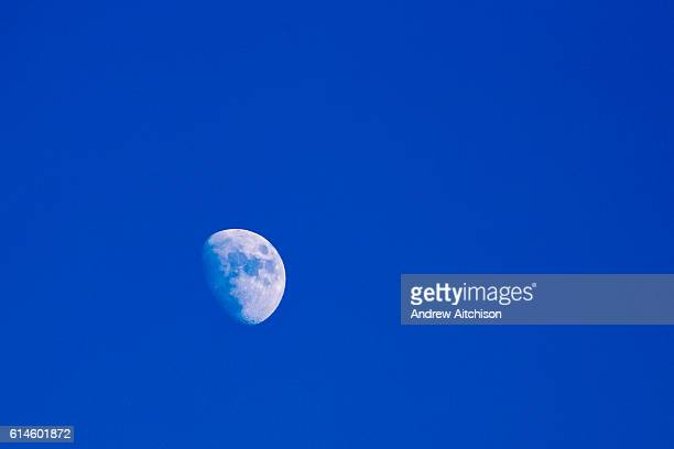 A 3/4 full moon appearing in the daytime during the winter months against a blue sky on the 19th of January 2016 Folkestone Kent United Kingdom