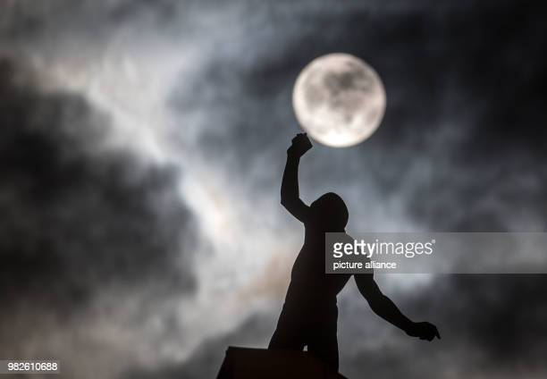 A full moon appears behind a thin veil of clouds above the sculpture Balance by the sculptor Hubertus von der Goltz on the roof of the exhibition...